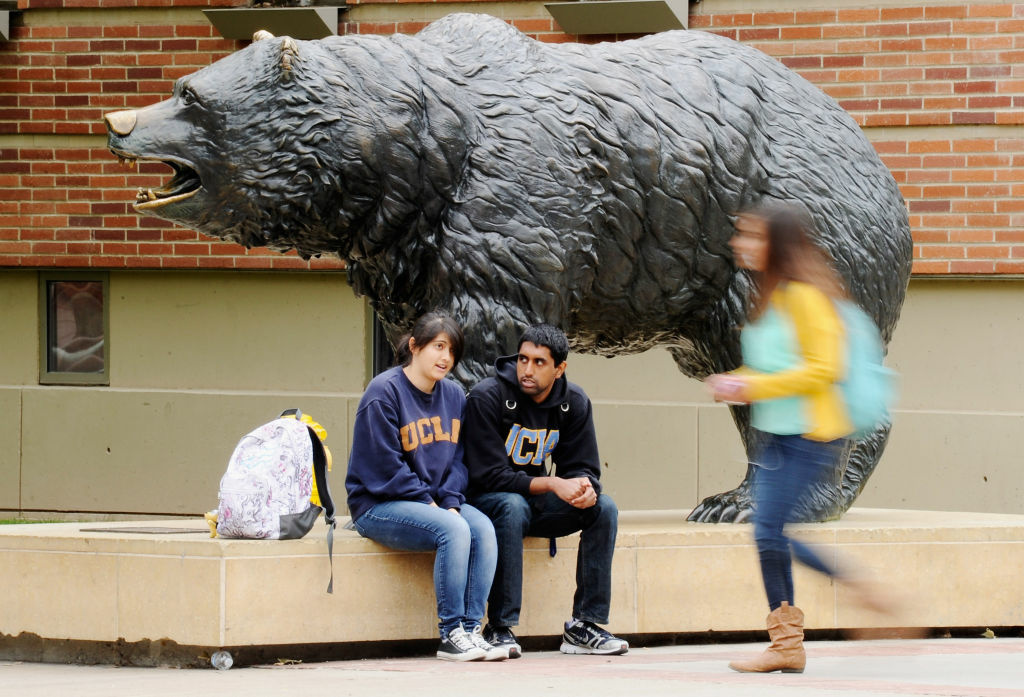 Students sit around the Bruin Bear statue during lunchtime on the campus of UCLA .