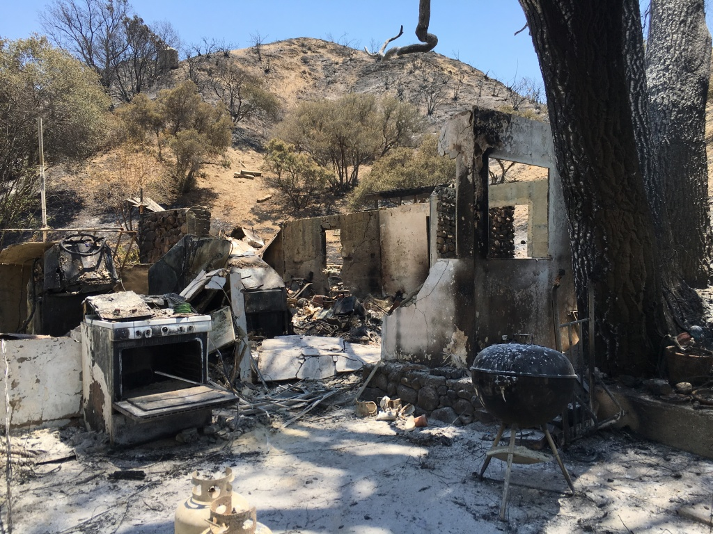 Christina Pease surveys what's left of her home in Sand Canyon. She and her husband had lived there for 17 years. The Sand Fire devoured it on Saturday.