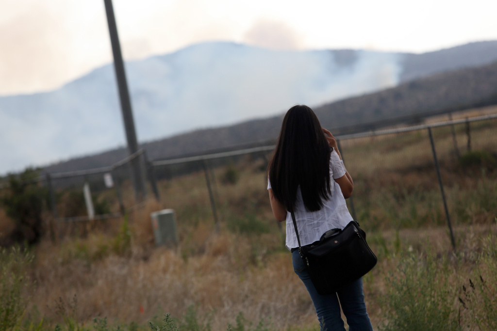 A woman looks at smoke from the Yarnell fire near a roadblock on the road to Yarnell, Arizona, on July 1, 2013. Reinforcements poured in Monday to battle a runaway wildfire which quadrupled in size overnight after killing 19 firefighters in one of the worst such incidents in US history. The Yarnell Hill fire -- which killed all but one member of a 20-strong 'hotshot' team -- was the biggest loss of firefighters' lives since the September 11 attacks, and the most from a US wildfire in 80 years.