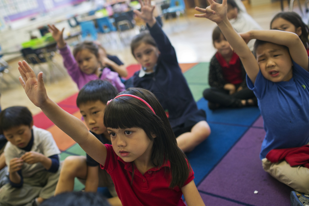 Kindergartener Mimi Echavez raises her hand to answer a question as teacher Tingting Mei reads a book to students at Eugene Field Elementary, a Mandarin immersion school in Pasadena, on Thursday morning, May 28, 2015.