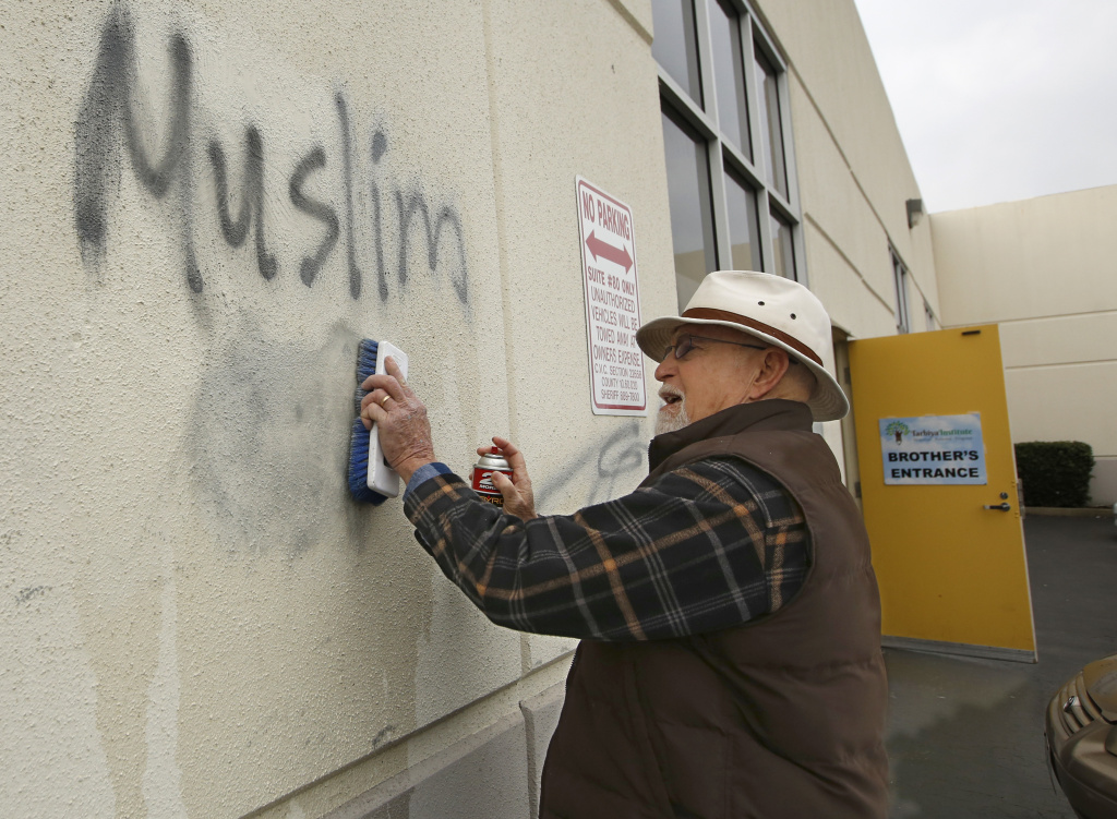 File: In this Feb. 1, 2017 file photo, Tom Garing cleans up racist graffiti painted on the side of a mosque in what officials are calling an apparent hate crime in Roseville, Calif. California's attorney general says the number of hate crimes increased about 11 percent last year, the second consecutive double-digit increase after years of decline. The report released Monday, July 3, 2017, shows 931 hate crimes statewide in 2016, nearly 100 more than in 2015.