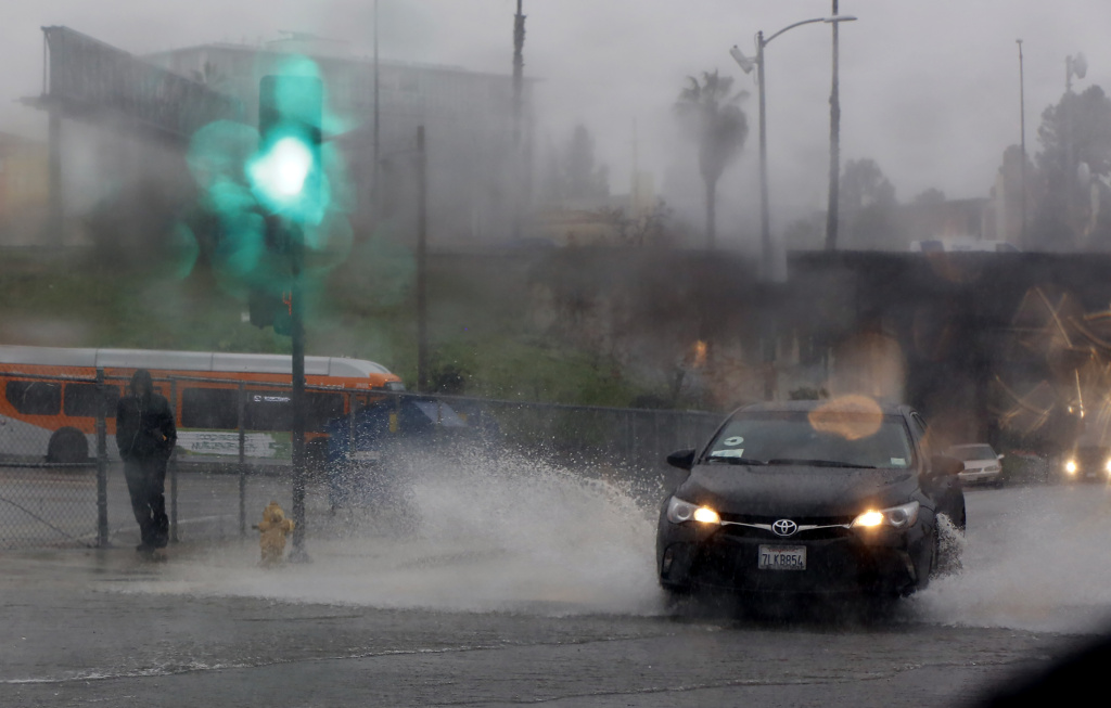 File: Raindrops bead upon a windshield as a pedestrian walks through rain in downtown Los Angeles, Friday, Jan. 20, 2017.