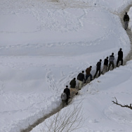 Survivors of an avalanche walk in the Abdullah Khil village of the Dara district of Panjshir province on Sunday. Nearly 200 people have been killed in north Afghanistan in some of the worst avalanches there for 30 years.