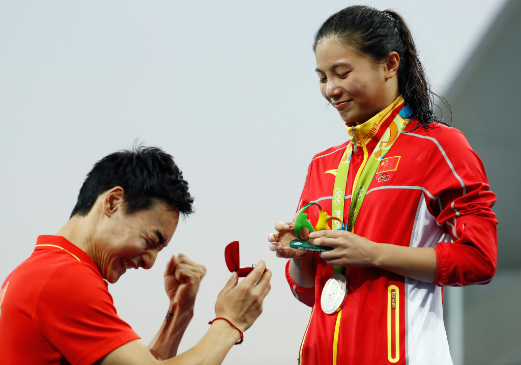 Chinese diver Qin Kai proposes to silver medalist He Zi of China on the podium during the medal ceremony for the Women's Diving 3m Springboard Final on Day 9 of the Rio 2016 Olympic Games at Maria Lenk Aquatics Centre on August 14, 2016 in Rio de Janeiro, Brazil.