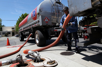 A gasoline tanker truck driver moves a hose as he transfers gasoline into an underground tank at a 76 gas station in San Anselmo, California.