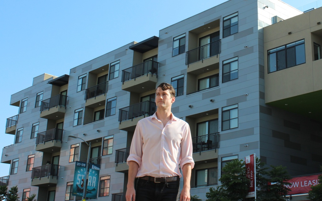 Brent Gaisford, 27, leads Abundant Housing LA, one of the area's YIMBY organizations. Behind him is the M Lofts in Palms, the kind of development he said L.A. should be building more of.
