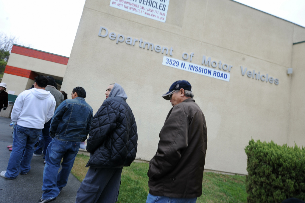 People wait in line outside of the State of California Department of Motor Vehicles (DMV) in Los Angeles, California on February 13, 2009.   The DMV, already infamous for long waiting times, is now further taxed as employees are off the job and the offices are closed two days a month as California government imposes its first-ever unpaid furlough to save money during the fiscal crisis.  The action is in connection with Schwarzenegger?s executive order that addresses the state?s 42 billion USD deficit and ongoing fiscal crisis.  Schwarzenegger has also threatened to lay off as many as 10,000 state employees if a new budget is not passed this week.  AFP PHOTO/ ROBYN BECK (Photo credit should read ROBYN BECK/AFP/Getty Images)
