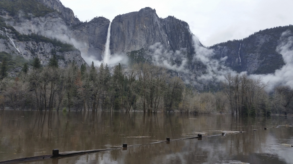 In this Saturday, April 7, 2018 photo released by the National Park Service, floodwaters cover Cooks Meadow and the pedestrian trail through Cooks Meadow in Yosemite Valley in Yosemite, Calif. Sections of Northside Drive, Southside Drive, and Sentinel Drive remain closed due to high water in the roadway. Parts of Yosemite National Park remained closed as the Merced River peaked several feet above flood stage through the Yosemite Valley.