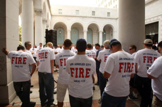 Los Angeles city fire fighters listen to public testimony over a loud speaker outside Los Angeles City Hall as the City Council considers a proposed $7.05-billion budget that slashes jobs to deal with the expected $530-million budget shortfall in 2009-2010 on May 18, 2009 in Los Angeles, California.
