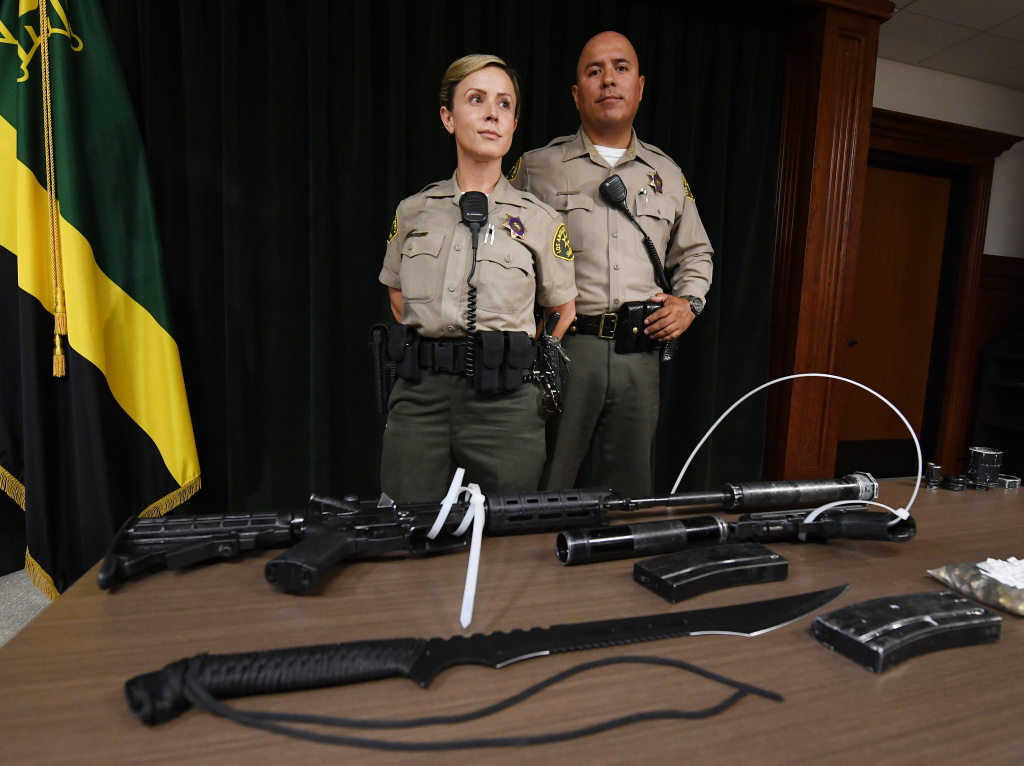 Los Angeles County Sheriff deputies show the media during a press conference the weapons seized after they arrested a man at the Sierra Madre Metro train station in Pasadena on June 21, 2017. The suspect was identified as 28-year-old Christopher Goodine. He was detained for urinating in public by sheriff's deputies, who discovered the armaments in a duffel bag. The weaponry included a loaded modified AR-15 rifle, a .40 calibre pistol, a machete and dozens of rounds of hollow point bullets.