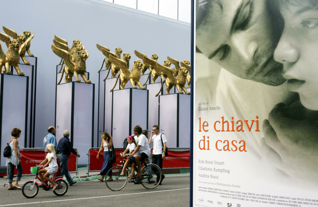 Tourists walk past a poster of Italian director's film Gianni Amelio