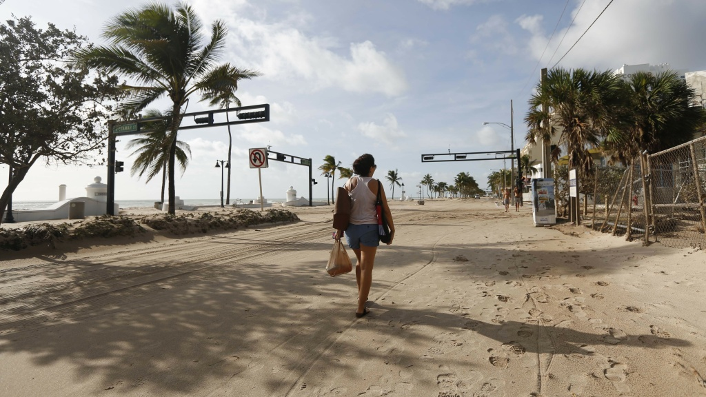 Hurricane Irma dumped water on towns — and covered oceanside streets with sand in several states. Here, Amela Desanto walks along Ft. Lauderdale Beach on Monday, as the storm headed inland.