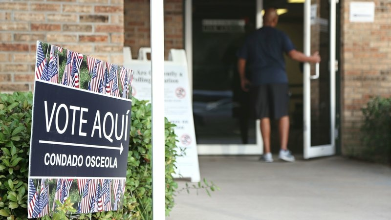 A voter enters an Osceola County polling station during early voting in the federal election in Kissimee, Florida on October 25, 2016.