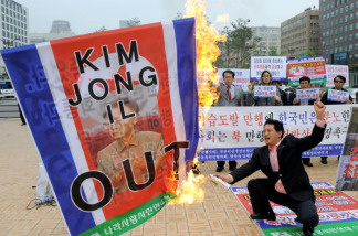 A South Korean conservative activist burns a North Korean flag showing a picture of its leader Kim Jong-Il during an anti-North Korea rally in Seoul on May 25, 2010 after South Korea announced reprisals against North Korea for the sinking of a warship.