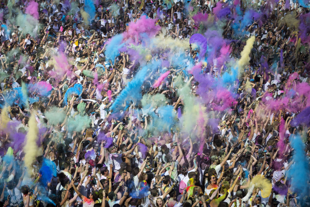 File:  People throw brightly-colored powder at the Holi Festival of Colours at Wembley Park on Aug. 13, 2016 in London, England.