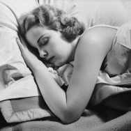 CIRCA 1950s: Woman sleeping in bed