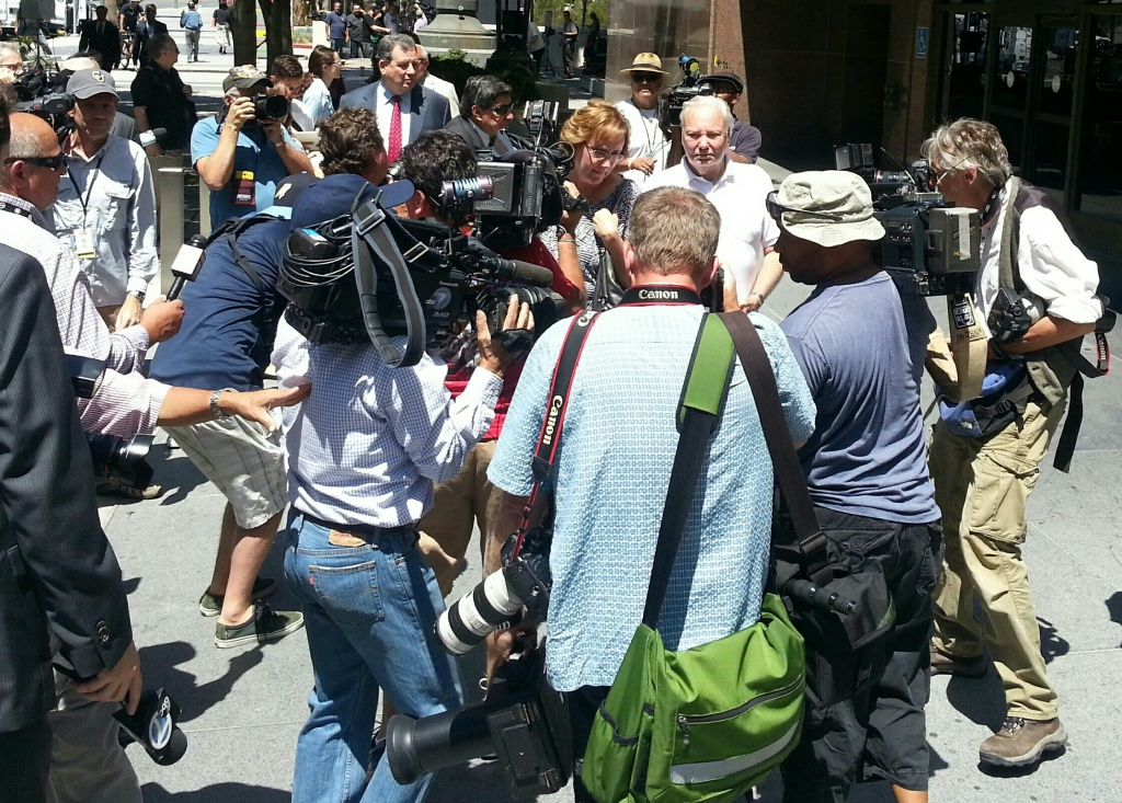 Bryan Stow's mother and father leave the downtown Los Angeles courthouse surrounded news photographers on Wednesday, July 9, 2014.