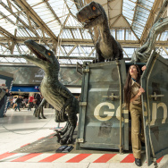 A dinosaur attendant emerges from a shipping container surrounded by dinosaurs during the 'Jurassic World' take over at Waterloo Station on June 8, 2015 in London, England.