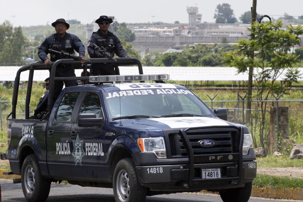 A unit of the Mexican Federal Police patrols the surroundings of the Puente Grande State prison (background) in Zapotlanejo, Jalisco State, Mexico, on 9 August, 2013 where former top Mexican cartel boss Rafael Caro Quintero -- who masterminded the kidnap and murder of a US anti-drug agent in 1985 -- was informed early Friday that a court ordered his release.
