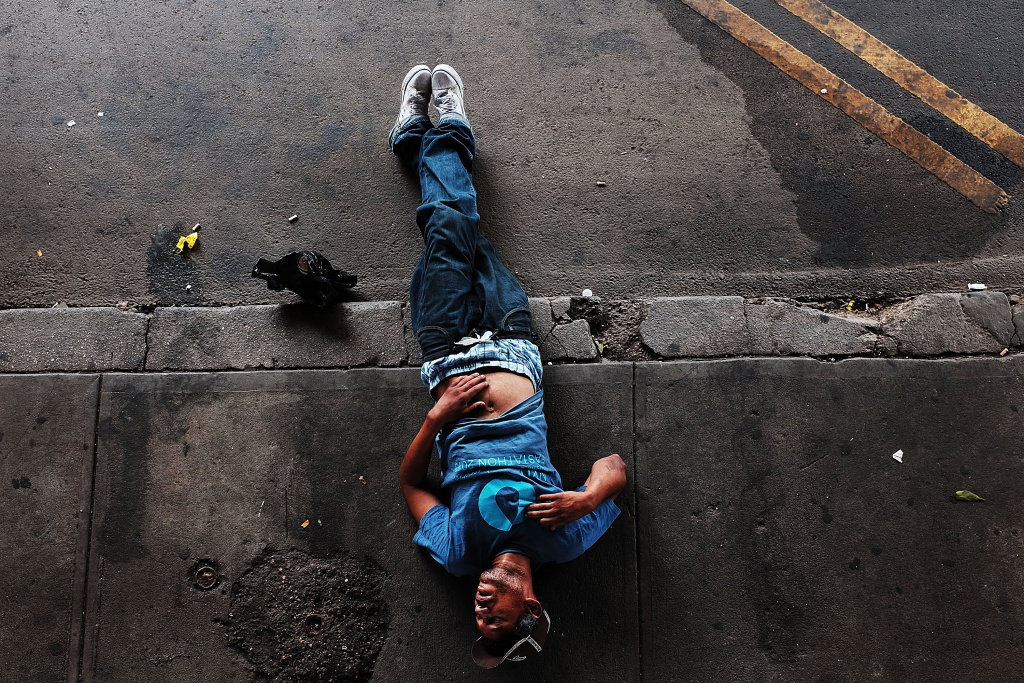 A passed out man lies on a sidewalk in New York, which has experienced an explosion in the use of K2 or 'Spice', a synthetic marijuana drug.