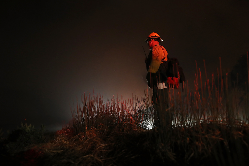 A firefighter monitors hot spots as the Thomas Fire burns in the Los Padres National Forest on December 8, 2017 near Ojai, California.