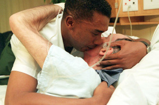 Quinton Booysen (L) hugs David Yates, his partner of 15 years, in a city hospital in Cape Town 08 May 2000.