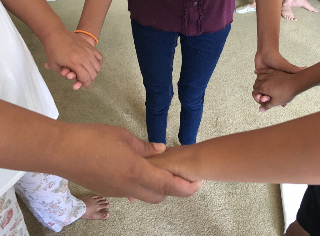 Irma, a migrant mother from Guatemala, holds hands with her young daughter and son at her sister's Reseda apartment in late July. The family is together again after they were separated by federal officials in May as part of President Trump's zero-tolerance border enforcement policies.