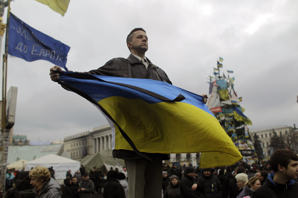 An anti-Yanukovych protester holds an Ukrainian flag in Kiev's Independence Square, the epicenter of the country's current unrest, Ukraine, Tuesday, Feb. 25, 2014. The Ukrainian parliament on Tuesday delayed the formation of a new government, reflecting political tensions and economic challenges following the ouster of the Russia-backed president. Parliament speaker Oleksandr Turchinov, who was named Ukraine's interim leader after President Viktor Yanukovych fled the capital, said that a new government should be in place by Thursday, instead of Tuesday, as he had earlier indicated.