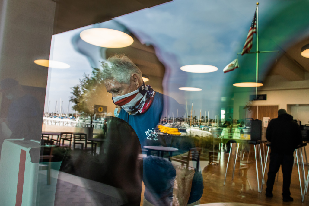 A man wearing an American flag face covering is seen through the window while he marks his ballot at Marina Park Community Vote Center on November 3, 2020 in Newport Beach, California.