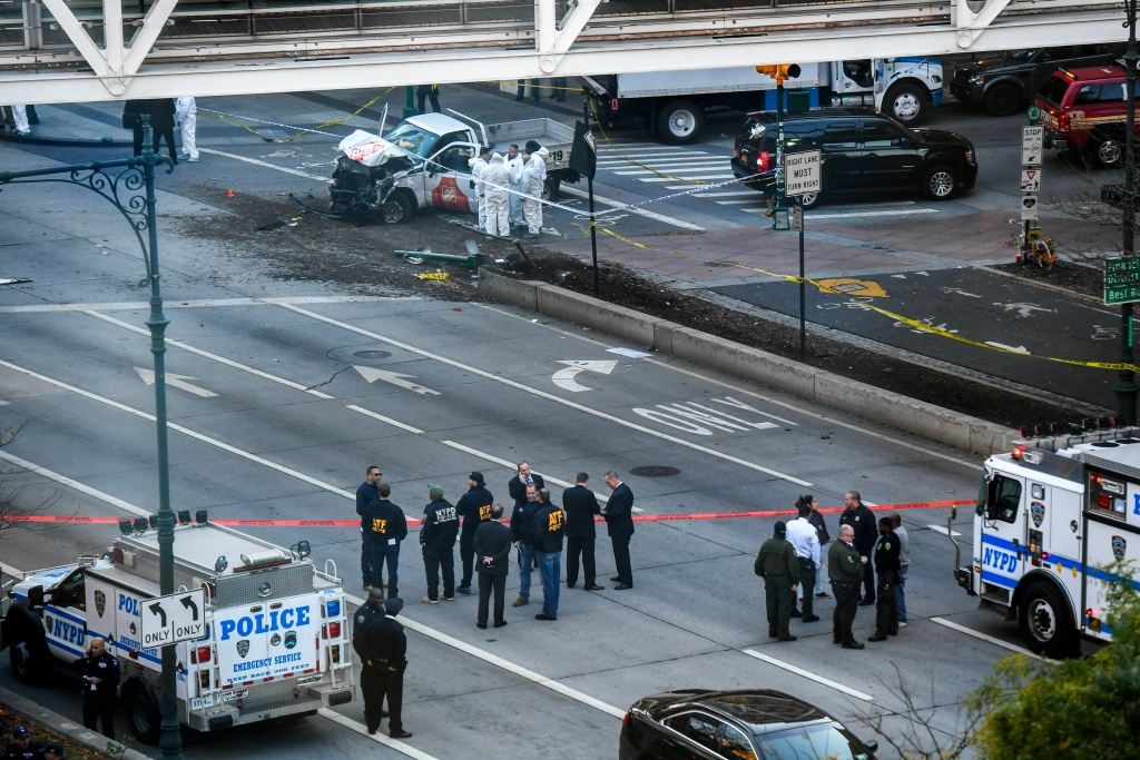Investigators inspect a truck following a shooting incident in New York on October 31, 2017.  Several people were killed and numerous others injured in New York on Tuesday when a suspect plowed a vehicle into a bike and pedestrian path in Lower Manhattan, and struck another vehicle on Halloween, police said. A suspect exited the vehicle holding up fake guns, before being shot by police and taken into custody, officers said. The motive was not immediately apparent.