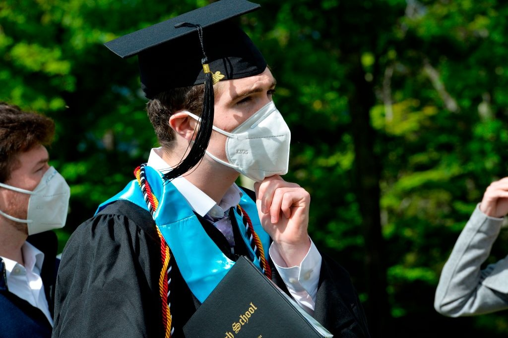 A student puts his mask back on after taking family photos during the Kenneth High School Class of 2020 Commencement Exercises at Cranmore Mountain in North Conway, New Hampshire on June 13, 2020.