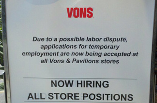 A sign outside of a Vons supermarket calls for applications for temporary employment.