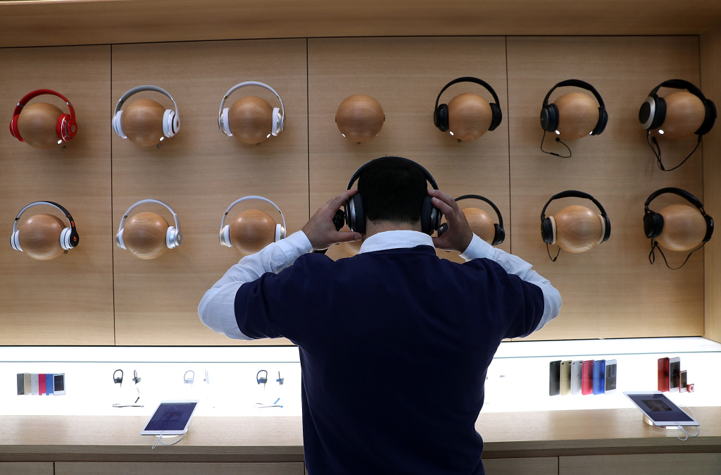 An Apple Store employee tries on a pair of headphones during a press preview of the new flagship Apple Store on May 19, 2016 in San Francisco, California.