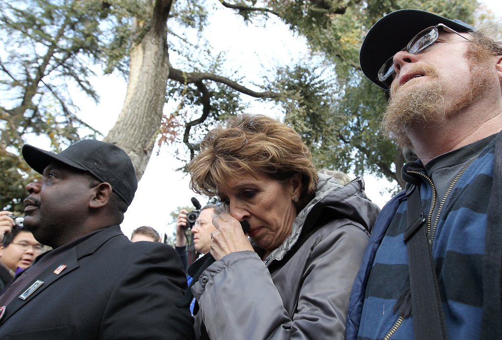 UC Davis Chancellor Linda Katehi (C) wipes her eye as she is escorted to a car after speaking to Occupy protestors during a demonstration at the UC Davis campus on November 21, 2011 in Davis, California.