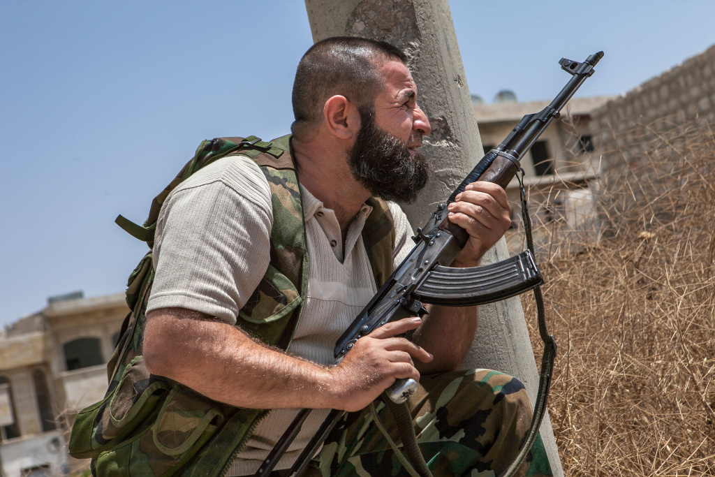 A Syrian rebel fighter belonging to the 'Martyrs of Maaret al-Numan' battalion holds a position on June 13, 2013 in the northwestern town of Maaret al-Numan in front of the army base of Wadi Deif, down in the valley.