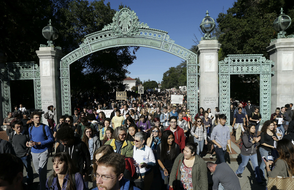 In this Nov. 24, 2014 file photo, students march under Sather Gate during a tuition hike protest at the University of California Berkeley in Berkeley, Calif., Monday, Nov. 24, 2014. High school seniors across the United States are spending much less time partying and socializing with friends than their parents' generation and report having a much lower sense of emotional well-being when they get to college, according to a new survey of college freshmen released Wednesday, Feb. 4, 2015. The annual survey conducted by UCLA's Higher Education Research Institute found that incoming students at four-year colleges and universities last fall devoted half as many hours to hanging out with friends during their final year of high school as students who entered college in 1987, when the institute first asked respondents about hobnobbing habits.