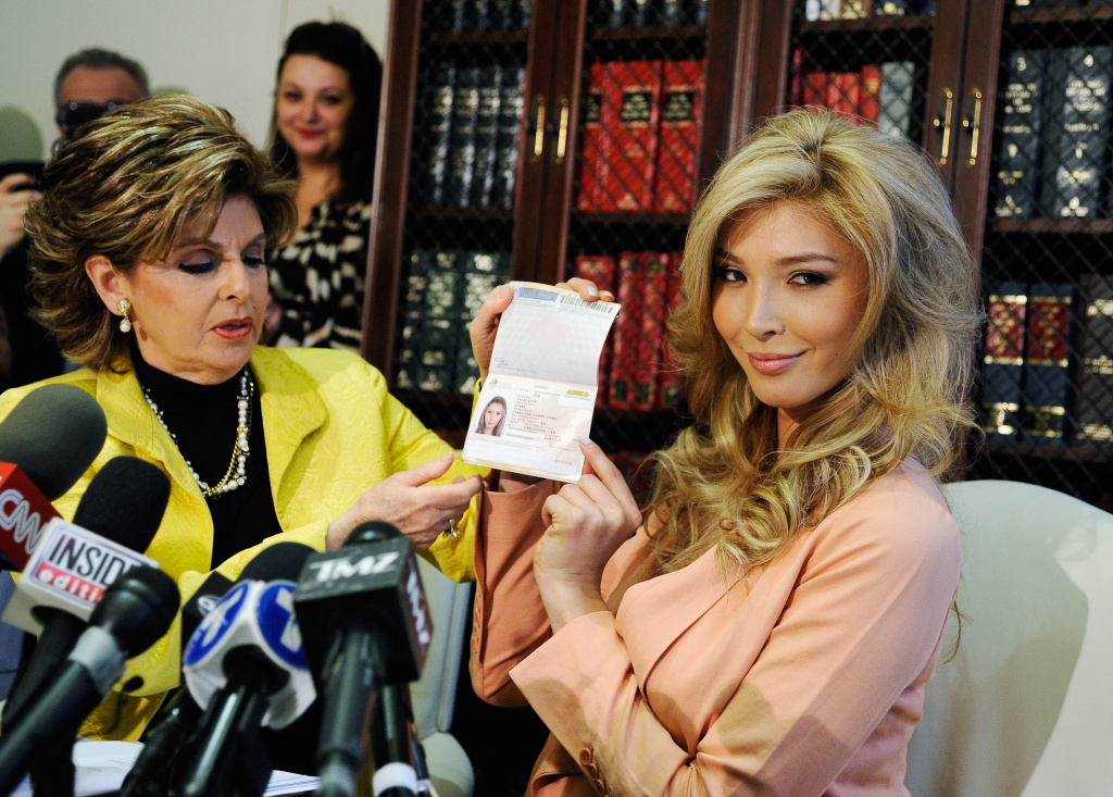 Jenna Talackova (R), a would be Miss Universe contestant, shows her Canadian passport, as a proof that she is a female, during a news conference with her attorney Gloria Allred on April 3, 2012 in Los Angeles, California.
