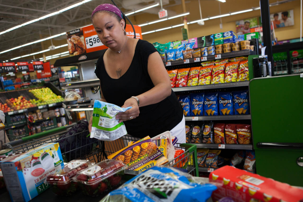 Sandi Vaughn unloads her cart, including two bins of strawberries, on to the checkout stand at a Walmart Neighborhood Market in Santa Clarita, Calif.