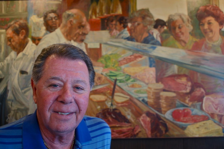 Norm Langer in front of the Marinus Welman's painting of Langer's Deli. Norm's father appears in the far left and Norm himself makes an appearance toward the top right.