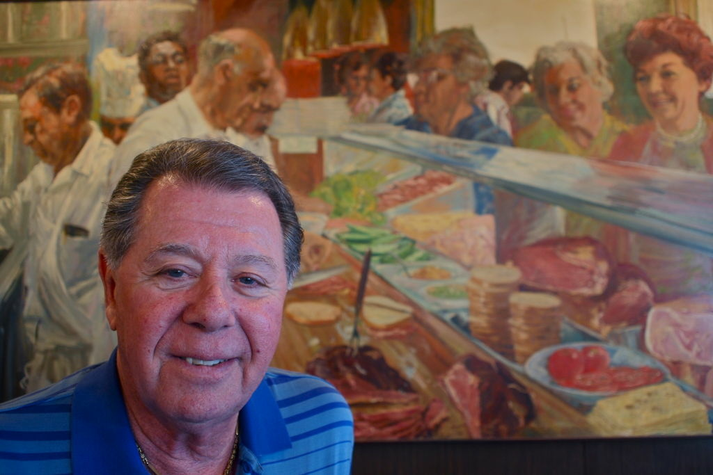 File: Norm Langer in front of the Marinus Welman's painting of Langer's Deli. Norm's father appears in the far left and Norm himself makes an appearance toward the top right.