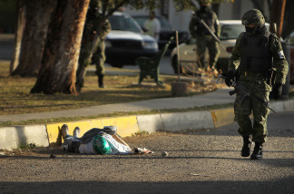 A member of the military police walks by a body with a mask in the street, one of numerous murders over a 24 hour period, on March 26, 2010 in Juarez, Mexico. The border city of Juarez, Mexico has been racked by violent drug related crime recently and has quickly become one of the most dangerous cities in the world to live.