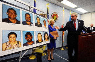 Los Angeles District Attorney Steve Cooley looks at a display of current and former City of Bell council members who were arrested on September 21, 2010 and face corruption charges.