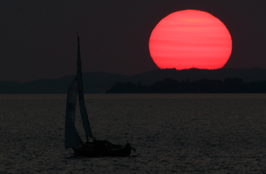 BREGENZ, AUSTRIA - JULY 12:  A sunset over the Bodensee (Lake Constance) is seen ahead of the rehearsal of the opera 'Die Zauberfloete' ('The Magic Flute') of Austrian composer Wolfgang Amadeus Mozart at Seebuehne on July 12, 2013 in Bregenz, Austria.  (Photo by Johannes Simon/Getty Images)