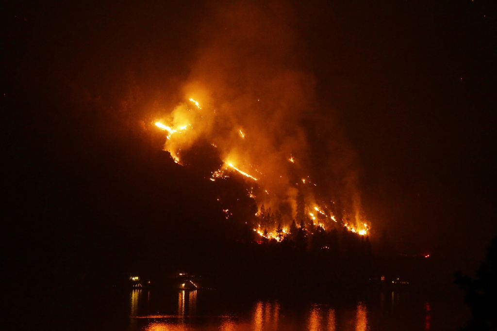 Timber burns in the First Creek fire near lakeside structures on the western shore of Lake Chelan late Monday, Aug. 17, 2015, near Chelan, Wash. Big wildfires threatened the Lake Chelan resort region of central Washington on Monday after driving away tourists, destroying a warehouse filled with nearly 2 million pounds of apples and forcing thousands of residents to flee.