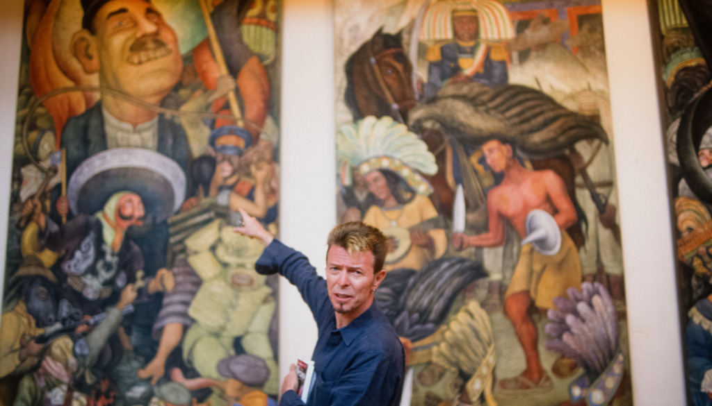 David Bowie points to a mural painted by Diego Rivera during his 1997 trip to Mexico.