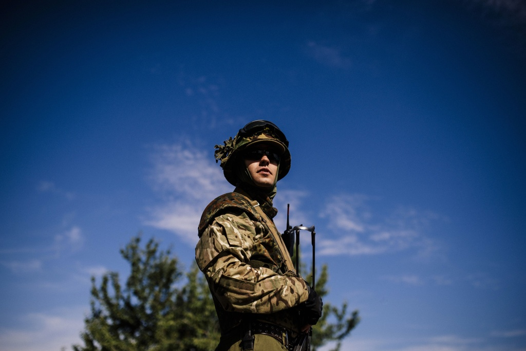 A Ukrainian soldier stands guard at a checkpoint on a road near the city of Dnepropetrovsk on August 25, 2014.