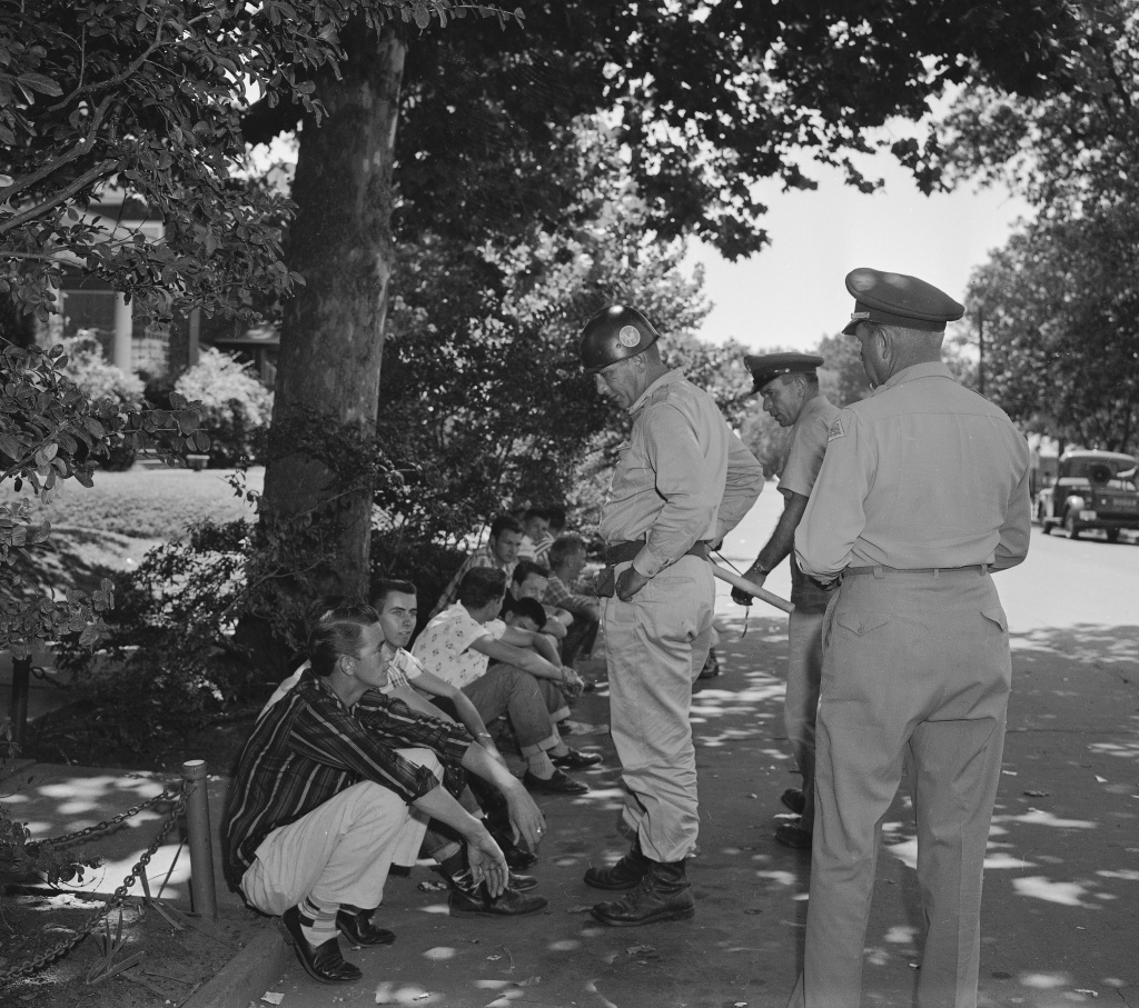 In this Sept. 5, 1957 file photo, teenagers who heckled passersby at Central High School in Little Rock, Ark., are held by National Guardsmen and told to either quiet down or be escorted from the scene.