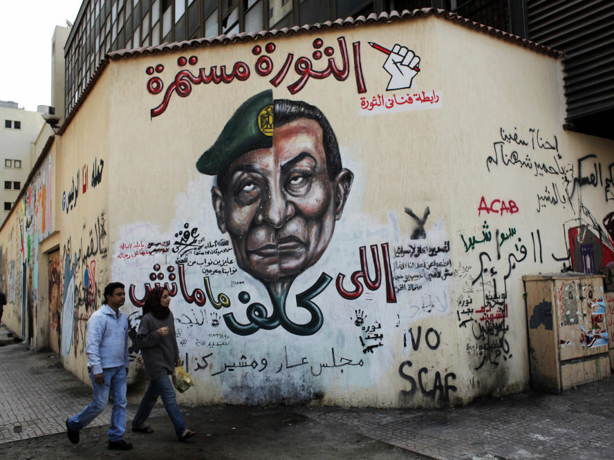 A mural in Cairo depicts the split faces of Egyptian military ruler Field Marshal Hussein Tantawi, left, and ousted president Hosni Mubarak accompanied by Arabic that reads,