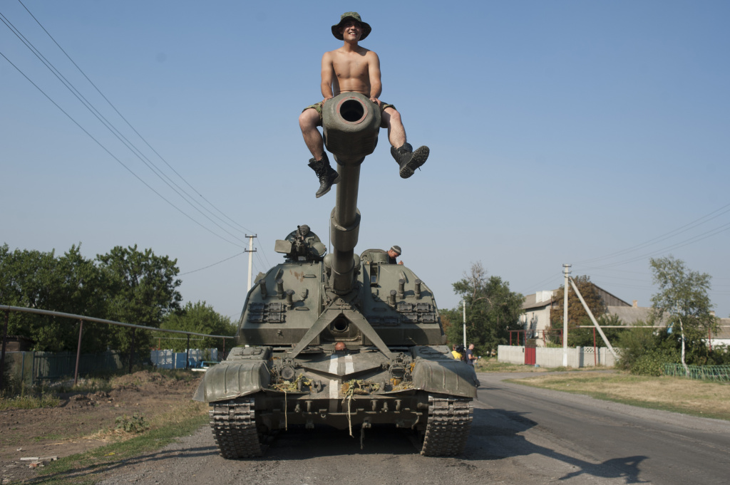 A Ukrainian soldier sits atop of a self-propelled gun as an army column of military vehicles prepares to roll to a frontline near Illovaisk, Donetsk region, eastern Ukraine.