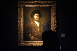 A visitor to Christie's looks at Rembrandt's 'Portrait of a man, half length, with arms akimbo' on December 4, 2009 in London.